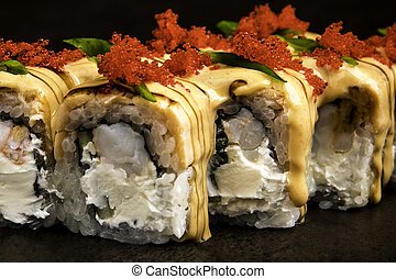 Portion of rolls with tobiko caviar in Japanese style on a dark background close up