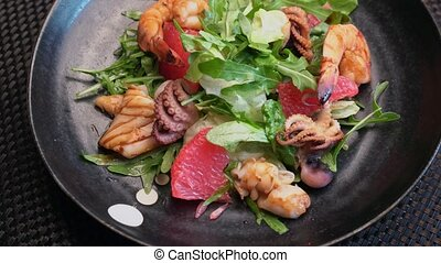 portion of seafood salad on a dark plate in the restaurant