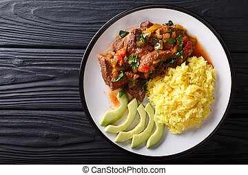 Portion of seco de chivo stewed goat meat with yellow rice and avocado close-up on a plate on the table. horizontal top view from above