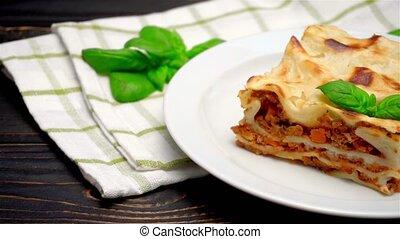 Portion of tasty lasagna on wooden backgound - Portion of...