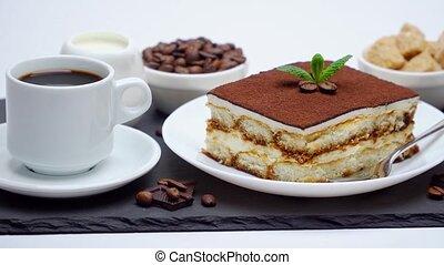 Portion of Traditional Italian Tiramisu dessert, cup of espresso and cream or milk on grey concrete background.