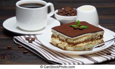 Portion of Traditional Italian Tiramisu dessert, cup of espresso, milk and coffee beans.