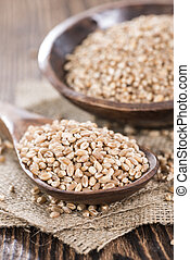 Portion of Wheat Grains (close-up shot) on dark wooden...