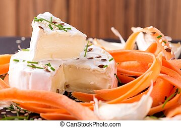 Portion of white camembert with carrot and chive