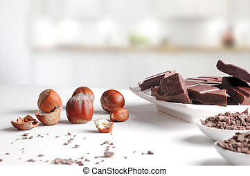 Portions and chocolate chips on containers with hazelnuts in kitchen