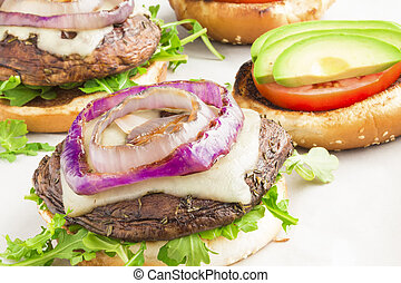 Portobello burgers on a bed of arugula, topped with melted swiss cheese, grilled purple onion, avocado and tomato