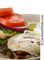 Portobello mushroom burger with red leaf lettuce, tomato and swiss cheese served open faced