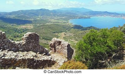 Ruin of the external walls around Volterraio Castle, oldest fortification on Elba Island, Tuscany, Italy, overlooking the gulf of Portoferraio. Panoramic views of Elba and Portoferraio city.