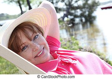 porträt, von, ältere frau, entspannend, in, liegestuhl