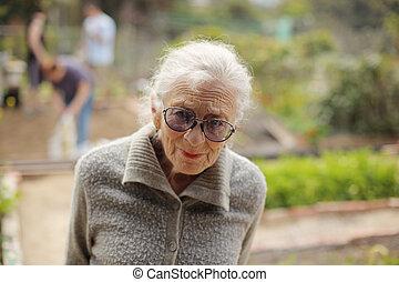 porträt, von, a, ältere frau, draußen, innen schauen, fotoapperat