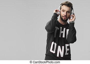 porträt, von, a, hübsch, junger mann, zuhören, musik, gegen, a, grau, hintergrund