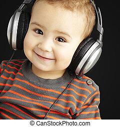 porträt, von, a, hübsch, kind, hören musik, und, lächeln,...