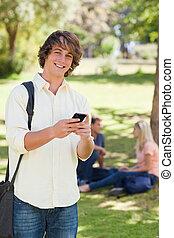 porträt, von, a, junger mann, gebrauchend, a, smartphone
