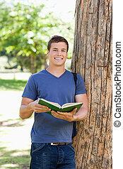 porträt, von, a, muscled, junger mann, halten buches