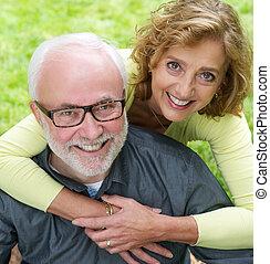 porträt, von, a, vorgesetztes ehepaar, lächelt, zusammen, draußen