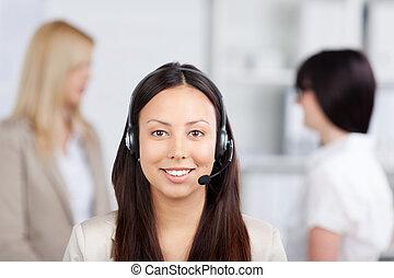 porträt, von, asiatische frau, kundendienstvertreter, tragender kopfhörer, mit, weibliche , mitarbeiter, in, hintergrund, in, buero