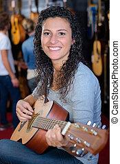 porträt, von, junge frau, spielende gitarre