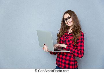 porträt, von, junger, lächelnde frau, stehende , und, besitz, laptop