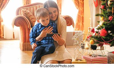 porträt, von, kleinkind, junge, wathcing, video, auf, handy, mit, mutter, an, wohnzimmer, dekoriert, für, weihnachten