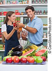 porträt, von, mittlerer erwachsener, mann, kunde, mit, verkäuferin, vergleichen, bellpepper, an, supermarkt