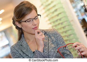 porträt, von, schöne frau, abnützende brille, in, optiker, kaufmannsladen