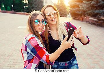 portré, közül, egy, boldog, két, mosolygós, lány, gyártás, selfie, fénykép, képben látható, smartphone., városi, háttér., a, este, napnyugta, felett, a, city.