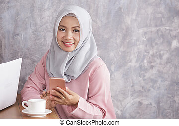 beautiful muslim women smiling while holding mobilephone