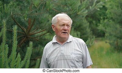 Portrain of old wrinkled man breathing evergreen leaves and smiling on a camera