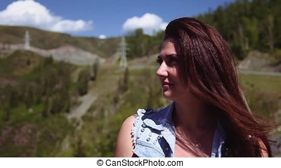 Portrait. A beautiful girl is sitting at a height and admiring the beautiful nature. The wind blows her hair. Slow motion