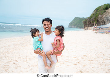 portrait a father carries his two daughter on the beach