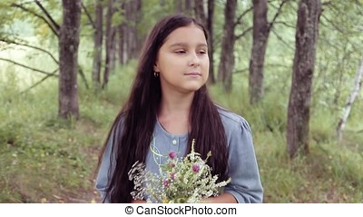 Portrait. A Little beautiful girl is walking on nature holding a bouquet of flowers in her hands and looking at it. Slow motion