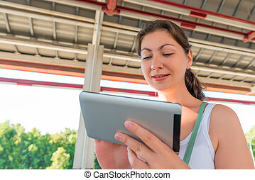 Portrait a pretty brunette with a tablet in hands