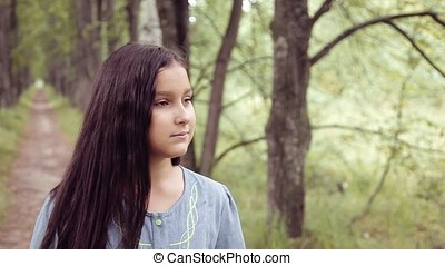 Portrait. A sweet beautiful little girl is sniffing a bouquet of flowers standing on nature in a summer sunny day while smiling with happiness looking at the camera