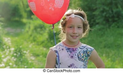 Portrait adorable girl with a balloon looking at the camera