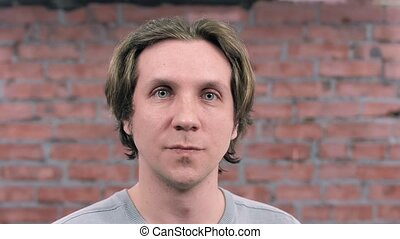Portrait adult man joyful shouting on camera. Brick wall on background. Audition