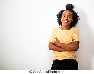 african american teenage girl smiling with arms crossed by white background