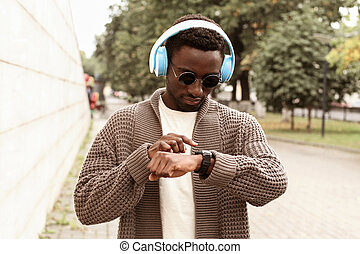 Portrait african man looking at smart watch using voice assistant or takes calling in wireless headphones on city street