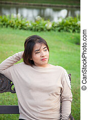 Portrait Asian woman sitting on the bench.