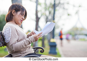 Portrait Asian woman sitting reading a document.