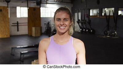 Portrait of an attractive, happy, athletic Caucasian woman with blonde hair in a ponytail cross training at a gym, taking a break, looking to camera and smiling