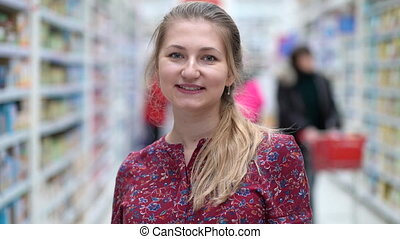 Portrait attractive young woman in supermarket marketplace