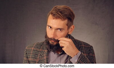 young man with beard posing on background in studio. handsome caucasian guy wearing casual shirt and trendy jacket. happy millennial looking at the camera and laughing points to the viewer