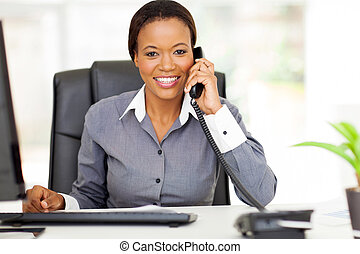 african american businesswoman using landline phone