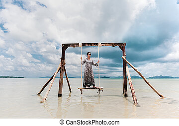 Portrait beautiful asian woman standing on hammock in the sea on vacation.