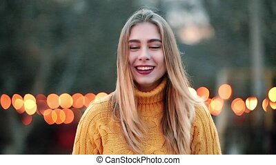 Portrait Beautiful blond shows positive gestures thumb laughs of orange lights wind blows in city
