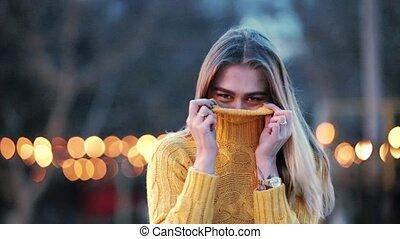 Portrait Beautiful blonde laughs shy closes clothes shows...
