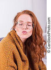 Portrait beautiful red-haired woman in orange cardigan with  kiss mouth