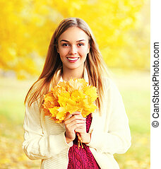 Portrait beautiful smiling woman with yellow maple leafs in sunny autumn day