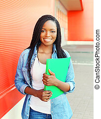 Portrait beautiful smiling young african woman with folder in city