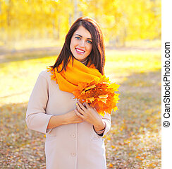 Portrait beautiful smiling young woman with yellow maple leafs in sunny autumn day